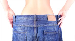 Woman jeans. Young woman in old jeans pant after losing weight Royalty Free Stock Photo