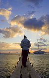 Woman on jetty at sunset. A woman walking along a jetty with yachts anchored in the bay at sunset Royalty Free Stock Photos