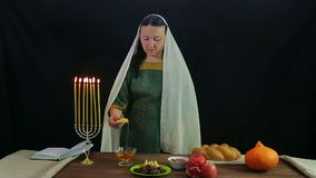 A woman of a dips a piece of apple into honey in honor of Rosh Hashanah and tries. Overall plan stock video footage