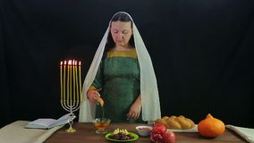 A woman of a dips a piece of apple into honey and tries. Overall plan stock video footage