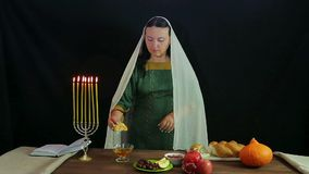 A woman of a takes a piece of a chalice, dips in honey and tries. stock video