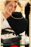 Woman at the jeweller. Is looking for jewellery Stock Images