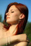 The woman with jeweller ornaments. The nude (naked) woman with jeweller ornaments over blew sky background Stock Photo