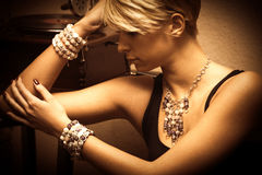 Woman and jewelry. Short hair blond elegant young woman portrait wearing jewelry, necklace and lot of bracelets, indoor shot, side view Royalty Free Stock Photo
