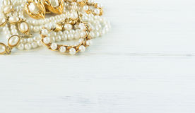Woman Jewelry. Vintage jewelry background. Beautiful gold and pearl necklaces, bracelets and earrings on white wood. Flat lay,. Top view Stock Images
