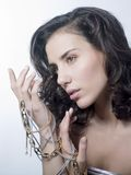 Woman and jewels. A very beautiful woman holding golden and silver chains between her fingers Stock Images