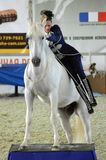 Woman jockey in blue dress International Horse Show. Female rider on a white horse. Riding hall Stock Image