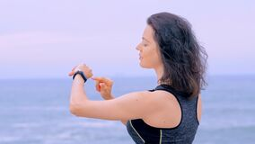 Woman jogger on beach doing exercises and looking data on fitness watch