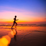 Woman jogger on the beach at sunset. Royalty Free Stock Image