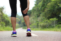Woman jogger hold her sports injured leg Stock Photography