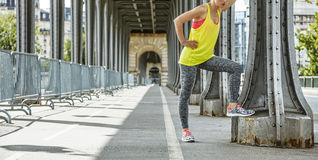 Woman jogger relaxing after workout on Pont de Bir-Hakeim bridge. Outdoors fitness in Paris. Closeup on young woman jogger relaxing after workout on Pont de Bir royalty free stock photography