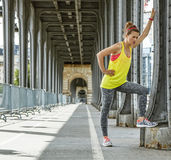 Woman jogger relaxing after workout on Pont de Bir-Hakeim bridge. Outdoors fitness in Paris. Full length portrait of young woman jogger relaxing after workout on royalty free stock images