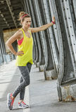 Woman jogger relaxing after workout on Pont de Bir-Hakeim bridge. Outdoors fitness in Paris. young woman jogger relaxing after workout on Pont de Bir-Hakeim royalty free stock photos