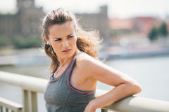 Woman jogger resting listening to music looking over shoulder Stock Image