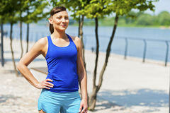 Woman jogger resting after run in city park by the river. Royalty Free Stock Image