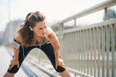 Woman jogger stretching on bridge while listening to music Royalty Free Stock Image