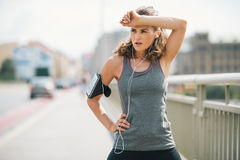 Woman jogger taking a break on bridge while wiping forehead Stock Photos