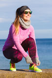 Woman jogger tying running shoes outdoor. Woman jogger wearing warm sporty clothes tying running shoes while jogging outdoor on seaside by cold day. Sport Royalty Free Stock Image