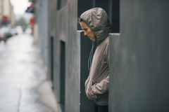 Woman jogger wearing rain gear wondering how long it will rain. A woman stands in the doorway of a modern building, wondering if the rain will stop any time soon Royalty Free Stock Images