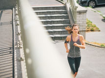 Woman jogger in the zone running along sidewalk Stock Photography