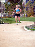 Woman jogging. Woman in workout clothing jogging on a suburban path Stock Photos