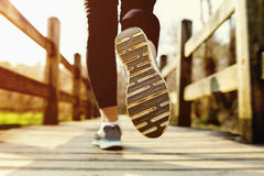 Woman jogging across an old country bridge at sunset Stock Photos