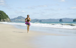 Woman jogging along a beautiful beach. Royalty Free Stock Image