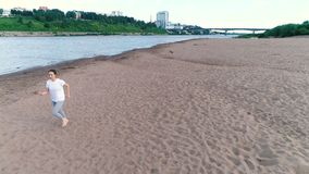 Woman jogging along the sandy beach of the river at sunset. Beautiful city view. stock video