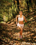 Woman in jogging attire. Of shorts and sports bra running up a path with fall foliage in the background stock images