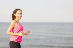 Woman jogging by beach with copy space Royalty Free Stock Images