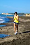 Woman jogging on the beach while listening music Stock Images