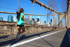 Woman jogging on Brooklyn Bridge, New York. A woman runs on the footpath of Brooklyn Bridge. Some other people are visible. In the background the cityscape of stock photo