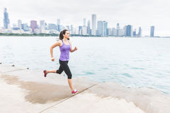 Woman jogging with Chicago skyline on background, panning Royalty Free Stock Photo