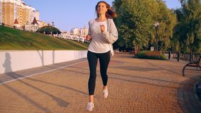 Girl running at sunset. Woman jogging in city park near her home caucasian smiling female wears grey hoodie looking camera with smile runs in the morning stock footage