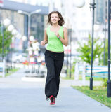 Woman jogging in city street park. Stock Photos