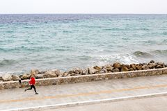 Woman jogging on city street at seaside Royalty Free Stock Images