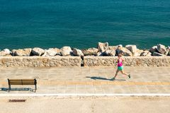 Woman jogging on city street at seaside Royalty Free Stock Image