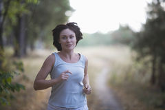 Woman Jogging On Dirt Road Royalty Free Stock Image