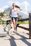Woman jogging dog. Happy woman jogging with her dog royalty free stock photo