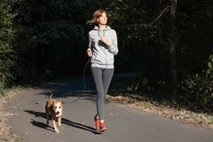 Woman jogging with dog in a park. Young female person with pet d. Oing running excercise in the forest royalty free stock photo