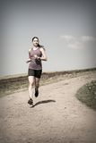 Woman jogging down gravel road Stock Images