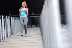 Free Woman Jogging Down On Stairs. Legs Workout At Stadium, Running On Stairs. Fitness And Health Concept Stock Photo - 53567830