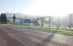 Woman jogging at early morning. Beautiful young woman exercise jogging and runing on athletic track on stadium at sunrise royalty free stock images