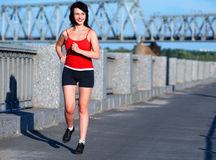Woman jogging at the embankment. In the sunny day stock photo