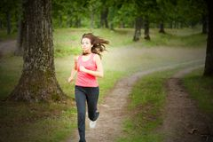 Woman jogging through a forest. Young woman running outdoor through a forest Royalty Free Stock Images