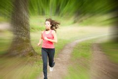 Woman jogging through a forest Royalty Free Stock Images