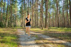 Woman jogging in forest Stock Photo