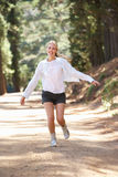 Woman jogging happily along a country lane. Smiling Royalty Free Stock Photos