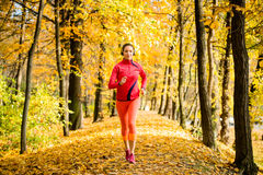 Woman jogging and listening music. Young woman with headphones  jogging in autumn nature and listening music Royalty Free Stock Photo