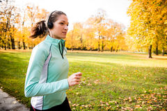 Woman jogging and listening music Stock Photos